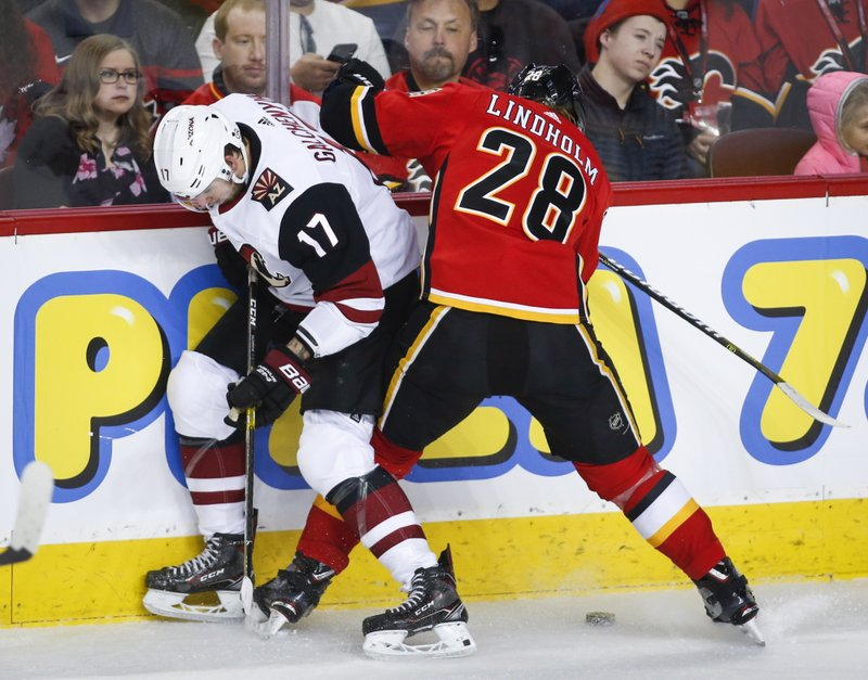 Arizona Coyotes' Alex Galchenyuk, left, battles for the puck with Calgary Flames' Elias Lindholm, of Sweden, during first period NHL hockey action in Calgary,  Calgary, Alberta, Monday, Feb. (Jeff McIntosh/The Canadian Press via AP)
