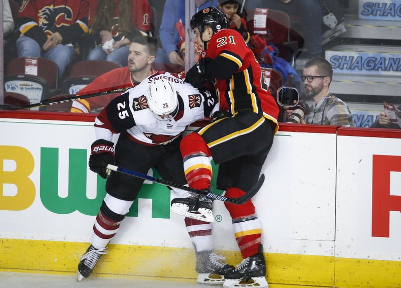 Arizona Coyotes' Nick Cousins, left, checks Calgary Flames' Garnet Hathaway during first period NHL hockey action in Calgary, Alberta, Monday, Feb. (Jeff McIntosh/The Canadian Press via AP)