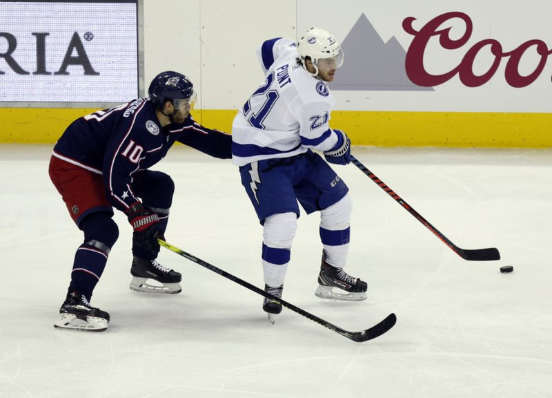 Tampa Bay Lightning defenseman Brayden Point, right, passes against Columbus Blue Jackets forward Alexander Wennberg, of Sweden, during the third period of an NHL hockey game in Columbus, Ohio, Monday, Feb. (AP Photo/Paul Vernon)