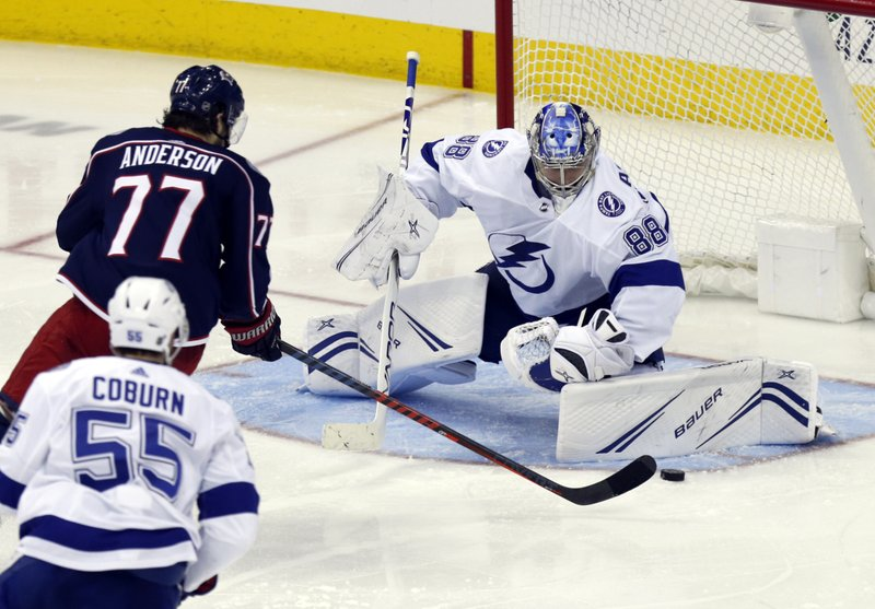 Tampa Bay Lightning goalie Andrei Vasilevskiy, right, of Russia, stops a shot by Columbus Blue Jackets forward Josh Anderson, center, as Lightning defenseman Braydon Coburn defends during the third period of an NHL hockey game in Columbus, Ohio, Monday, Feb. (AP Photo/Paul Vernon)