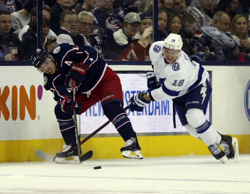 Columbus Blue Jackets forward Cam Atkinson, left, passes against Tampa Bay Lightning forward Ondrej Palat, of the Czech Republic, during the second period of an NHL hockey game in Columbus, Ohio, Monday, Feb. (AP Photo/Paul Vernon)