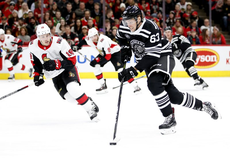 Chicago Blackhawks defenseman Carl Dahlstrom (63) skates with the puck past Ottawa Senators left wing Ryan Dzingel (18) during the first period of an NHL hockey game Monday, Feb. (AP Photo/Jeff Haynes)