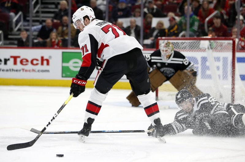 Chicago Blackhawks defenseman Erik Gustafsson (56) pokes the puck away from Ottawa Senators center Chris Tierney (71) during the first period of an NHL hockey game Monday, Feb. (AP Photo/Jeff Haynes)