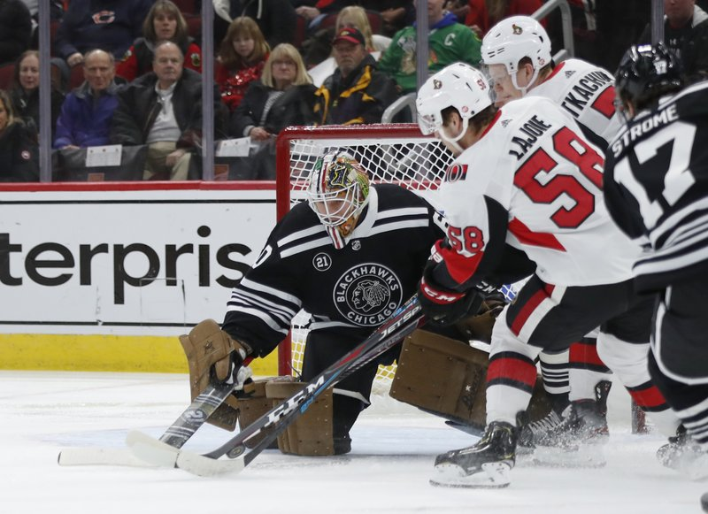 Chicago Blackhawks goaltender Collin Delia (60) makes a stop on Ottawa Senators defenseman Maxime Lajoie (58) during the first period of an NHL hockey game Monday, Feb. (AP Photo/Jeff Haynes)