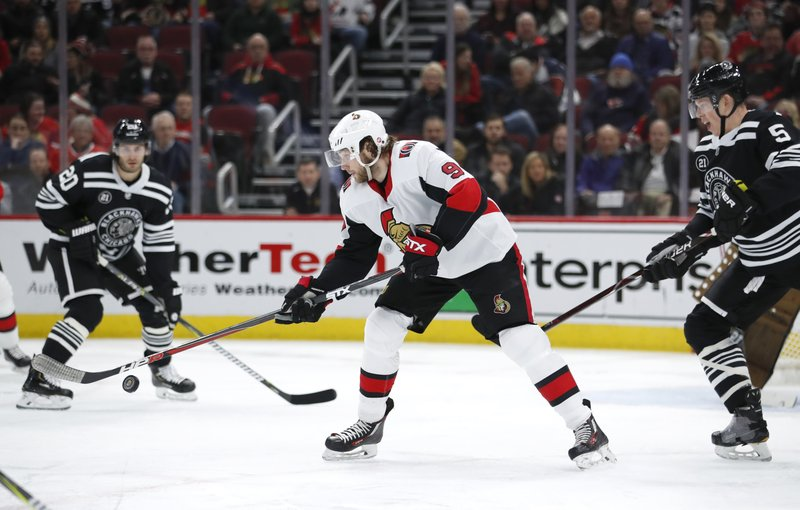 Ottawa Senators right wing Bobby Ryan (9) knocks the puck out of the air as Chicago Blackhawks defenseman Connor Murphy (5) defends during the first period of an NHL hockey game Monday, Feb. (AP Photo/Jeff Haynes)