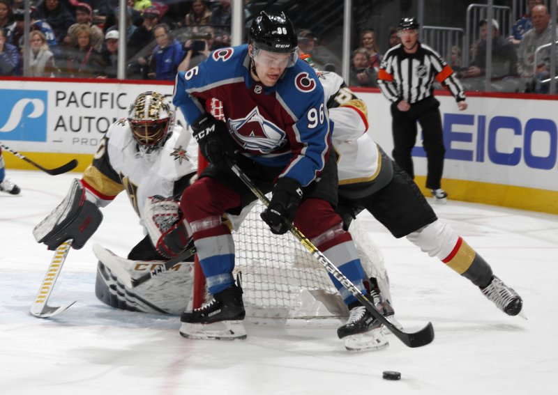 Colorado Avalanche right wing Mikko Rantanen, front, wraps around the net past Vegas Golden Knights defenseman Nate Schmidt to put a shot on goaltender Malcolm Subban in the first period of an NHL hockey game Monday, Feb. (AP Photo/David Zalubowski)