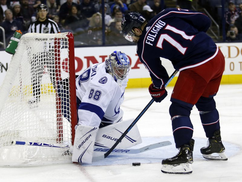 Tampa Bay Lightning goalie Andrei Vasilevskiy, left, of Russia, stops a shot by Columbus Blue Jackets forward Nick Foligno during the second period of an NHL hockey game in Columbus, Ohio, Monday, Feb. (AP Photo/Paul Vernon)