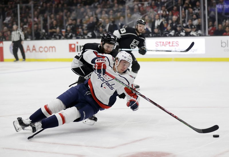 Washington Capitals' Jakub Vrana, bottom, falls as he reaches for the puck in front of Los Angeles Kings' Derek Forbort during the first period of an NHL hockey game Monday, Feb. (AP Photo/Marcio Jose Sanchez)