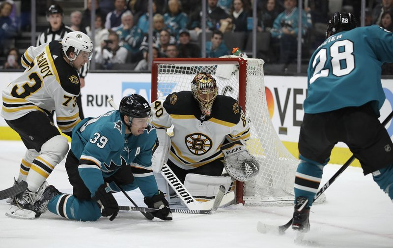 Boston Bruins goalie Tuukka Rask (40) and Charlie McAvoy, left, defend against San Jose Sharks' Logan Couture (39) and Timo Meier, right, during the first period of an NHL hockey game Monday, Feb. (AP Photo/Ben Margot)