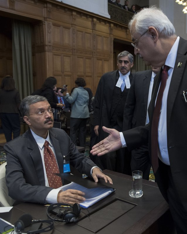 Pakistan's attorney general Anwar Mansoor Khan, right, greets Deepak Mittal, the joint secretary of India's Foreign Ministry, prior to India presenting oral arguments at the International Court of Justice, or World Court, in The Hague, Netherlands, Monday, Feb. (AP Photo/Peter Dejong)