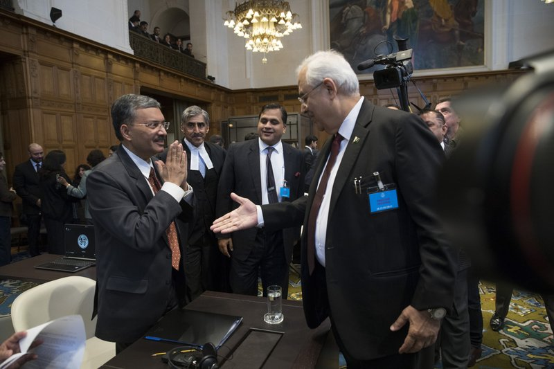 Pakistan's attorney general Anwar Mansoor Khan, right, greets Deepak Mittal, the joint secretary of India's Foreign Ministry, as he present oral arguments at the International Court of Justice, or World Court, in The Hague, Netherlands, Monday, Feb. (AP Photo/Peter Dejong)