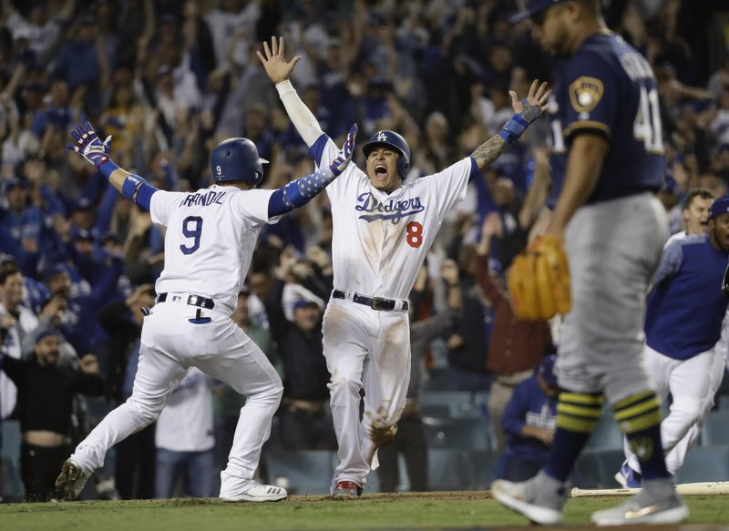 FILE - In this Oct. 16, 2018, file photo, Los Angeles Dodgers' Manny Machado (8) reacts after scoring on a Cody Bellinger walk-off hit during the 13th inning of Game 4 of the National League Championship Series baseball game against the Milwaukee Brewers, in Los Angeles. (AP Photo/Matt Slocum, File)