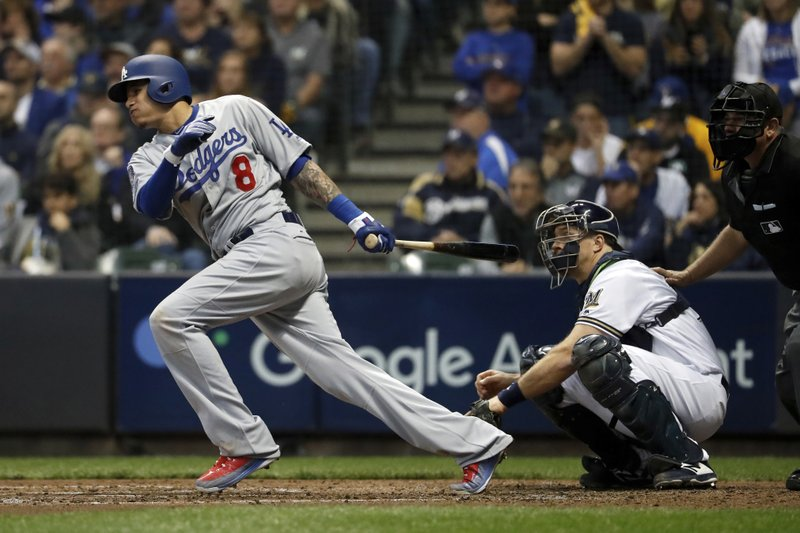 FILE - In this Oct. 20, 2018, file photo, then-Los Angeles Dodgers' Manny Machado (8) hits a single during the fourth inning of Game 7 of the National League Championship Series baseball game against the Milwaukee Brewers, in Milwaukee. (AP Photo/Jeff Roberson, File)