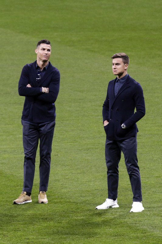 Juventus players Paulo Dybala, right, and Cristiano Ronaldo, stand on the pitch, after their arrival at Wanda Metropolitano stadium in Madrid, Spain, Tuesday, Feb. (AP Photo/Andrea Comas)