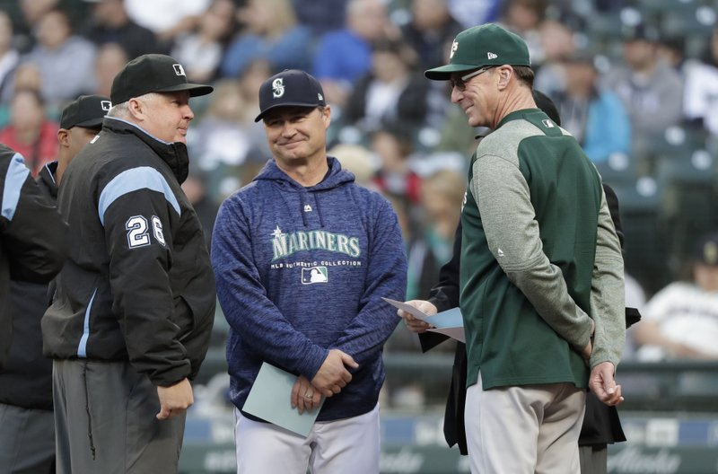 FILE - In this May 1, 2018, file photo, umpire Bill Miller, left, talks with Seattle Mariners manager Scott Servais, center, and Oakland Athletics manager Bob Melvin before a baseball game, in Seattle. (AP Photo/Elaine Thompson, File)