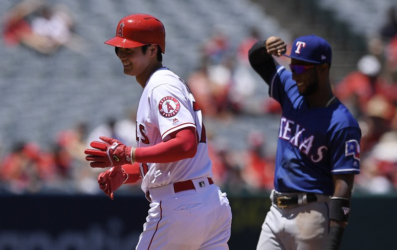 FILE - In this June 3, 2018, file photo, Los Angeles Angels' Shohei Ohtani, left, of Japan, smiles as he talks to Texas Rangers shortstop Jurickson Profar while standing on second during the second inning of a baseball game, in Anaheim, Calif. (AP Photo/Mark J. Terrill, File)
