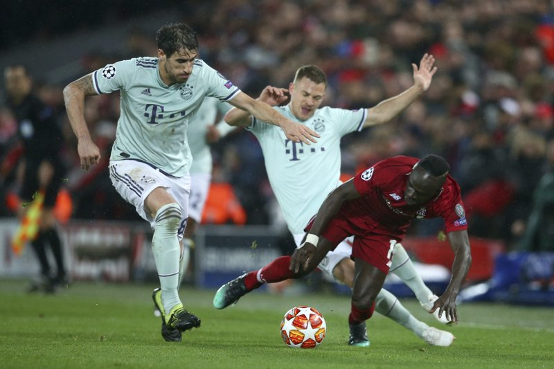 Liverpool's Sadio Mane, right, competes for the ball with Bayern midfielder Javi Martinez, left, and Bayern midfielder Joshua Kimmich, back center, during the Champions League round of 16 first leg soccer match between Liverpool and Bayern Munich at Anfield stadium in Liverpool, England, Tuesday, Feb. (AP Photo/Dave Thompson)
