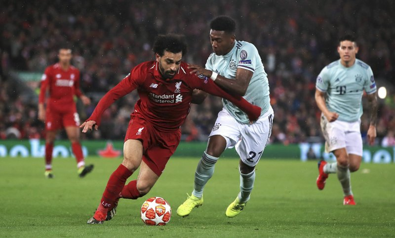 Liverpool's Mohamed Salah , left and Bayern Munich's David Alaba battle for the ball, during the Champions League round of 16 first leg soccer match between Liverpool and Bayern Munich,  at Anfield, in Liverpool, England, Tuesday, Feb. (Peter Byrne/PA Wire/PA via AP)