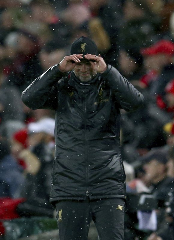 Liverpool head coach Juergen Klopp holds his cap during the Champions League round of 16 first leg soccer match between Liverpool and Bayern Munich at Anfield stadium in Liverpool, England, Tuesday, Feb. (AP Photo/Dave Thompson)