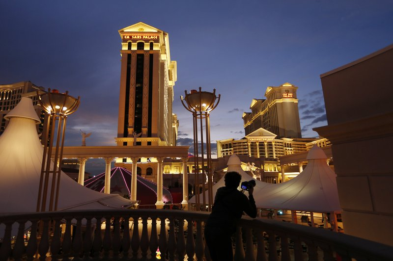 FILE - In this Monday, Jan. 12, 2015, file photo, a man takes pictures of Caesars Palace hotel and casino, in Las Vegas. (AP Photo/John Locher, File)