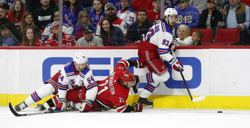 Carolina Hurricanes' Nino Niederreiter (21) of Switzerland battles the New York Rangers' Adam McQuaid (54) and Mika Zibanejad (93) of Sweden for the puck during the second period of an NHL hockey game in Raleigh, N. (AP Photo/Chris Seward)