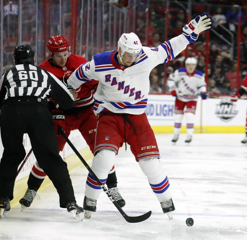 Carolina Hurricanes' Lucas Wallmark (71) of Sweden battles New York Rangers' Brendan Smith (42) during the second period of an NHL hockey game in Raleigh, N. (AP Photo/Chris Seward)