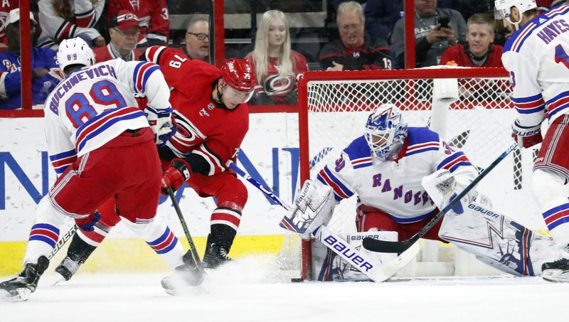 Carolina Hurricanes' Micheal Ferland (79) is defended by New York Rangers' Pavel Buchnevich (89) from Russia and Henrik Lundqvist (30) of Sweden during the first period of an NHL hockey game in Raleigh, N. (AP Photo/Chris Seward)