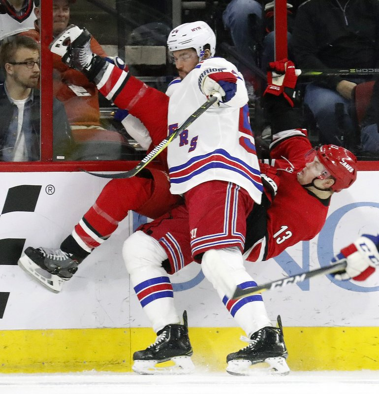 Carolina Hurricanes' Warren Foegele (13) and New York Rangers' Adam McQuaid (54) collide along the boards during the first period of an NHL hockey game in Raleigh, N. (AP Photo/Chris Seward)
