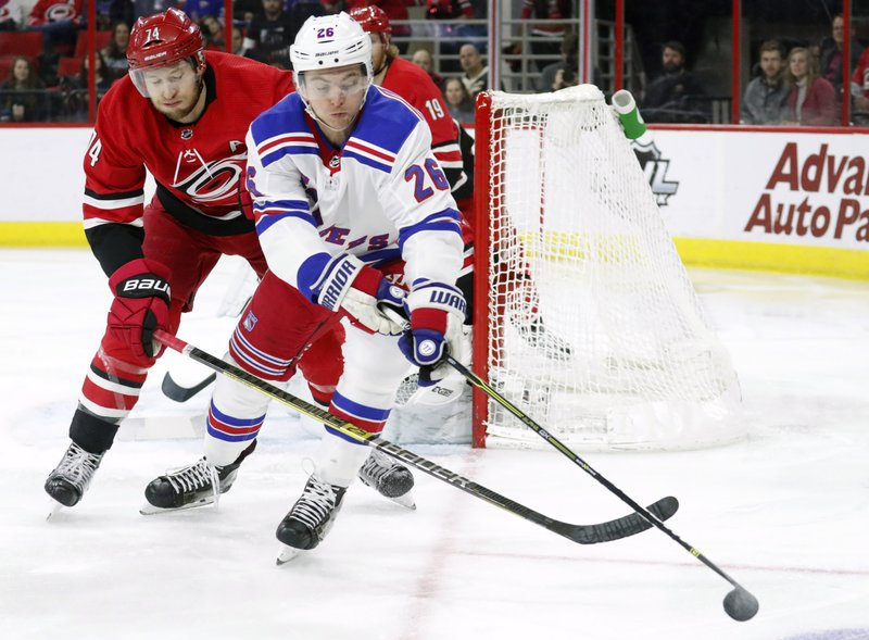 Carolina Hurricanes' Jaccob Slavin, left, and New York Rangers' Jimmy Vesey, right,  vie for the puck during the first period of an NHL hockey game in Raleigh, N. (AP Photo/Chris Seward)