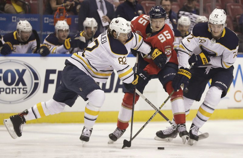 Buffalo Sabres defenseman Nathan Beaulieu, left, Florida Panthers center Henrik Borgstrom, center, and Sabres right wing Tage Thompson, right, compete for the puck during the first period of an NHL hockey game Tuesday, Feb. (AP Photo/Brynn Anderson)
