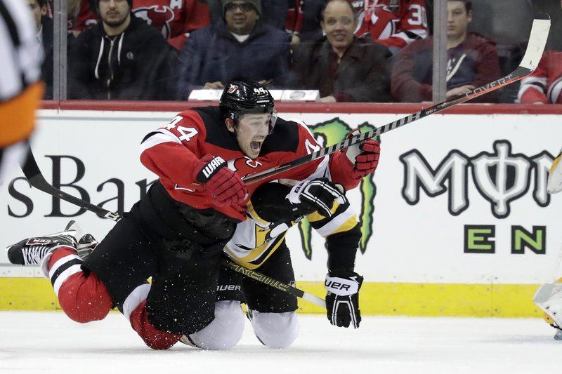 New Jersey Devils left wing Miles Wood, left, falls to the ice while competing for the puck with Pittsburgh Penguins right wing Bryan Rust during the first period of an NHL hockey game, Tuesday, Feb. (AP Photo/Julio Cortez)