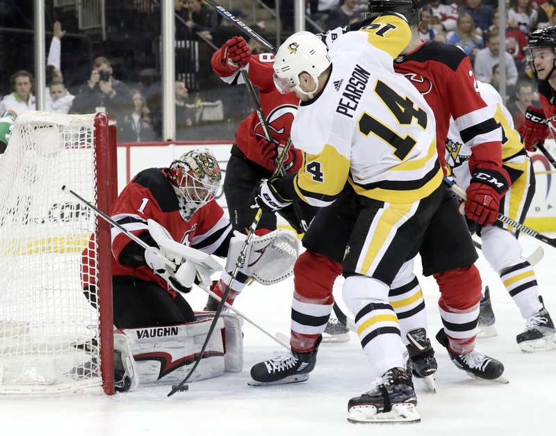 New Jersey Devils goaltender Keith Kinkaid (1) stops a shot s Pittsburgh Penguins left wing Tanner Pearson (14) attacks during the first period of an NHL hockey game, Tuesday, Feb. (AP Photo/Julio Cortez)