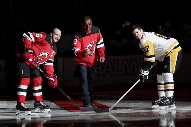Actor Patrick Warburton, center, is dressed as Seinfeld cast member David Puddy, during a ceremonial puck drop with New Jersey Devils defenseman Andy Greene, left, and Pittsburgh Penguins center Sidney Crosby prior to an NHL hockey game, Tuesday, Feb. (AP Photo/Julio Cortez)
