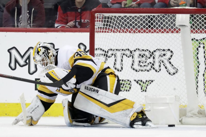 A shot by New Jersey Devils left wing Miles Wood, not visible, gets by Pittsburgh Penguins goaltender Matt Murray for a goal during the third period of an NHL hockey game, Tuesday, Feb. (AP Photo/Julio Cortez)