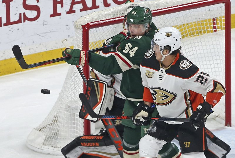 Minnesota Wild's Mikael Granlund, left, of Finland, tries to bat down the puck on a wide shot as Anaheim Ducks' Brandon Montour defends in the first period of an NHL hockey game Tuesday, Feb. (AP Photo/Jim Mone)