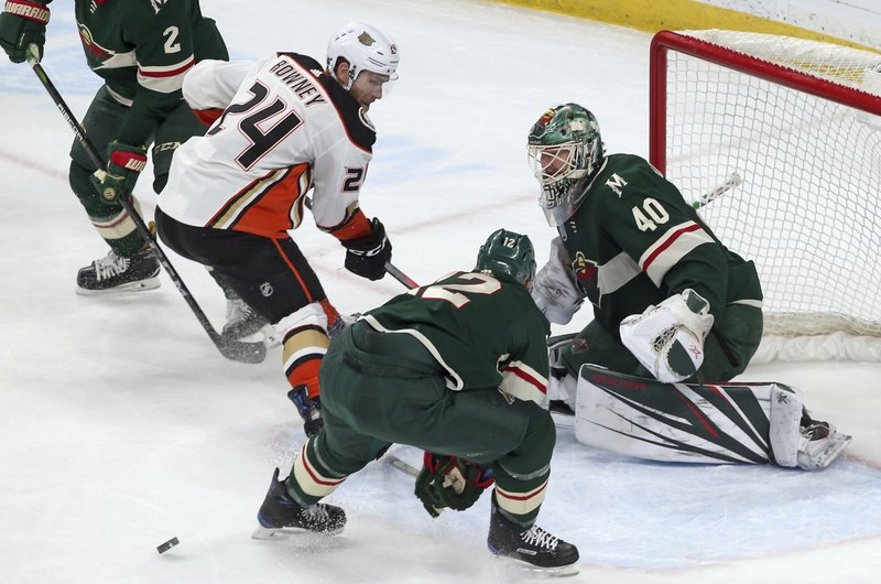 Anaheim Ducks' Carter Rowney, left, positions himself for a pass as Minnesota Wild goalie Devan Dubnyk, right, and Eric Staal defends in the first period of an NHL hockey game Tuesday, Feb. (AP Photo/Jim Mone)