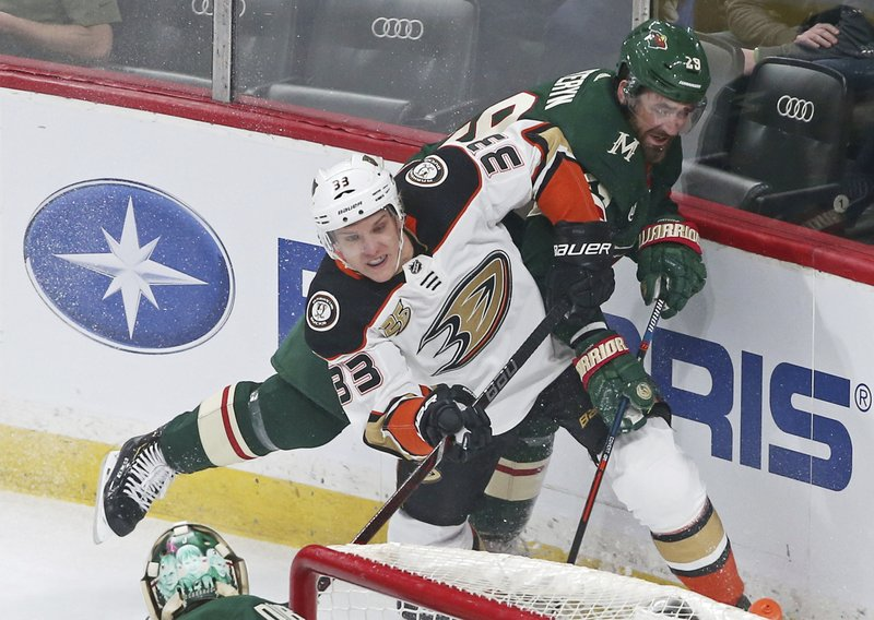 Anaheim Ducks' Jakob Silfverberg, left, of Sweden, squeezes out Minnesota Wild's Greg Pateryn, right, in the first period of an NHL hockey game Tuesday, Feb. (AP Photo/Jim Mone)