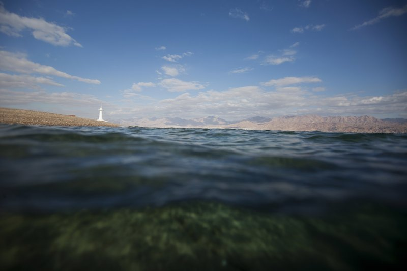 This Monday, Feb. 11, 2019 photo, shows a diver's view of the Red Sea with a marine observatory in the distance, in the Red Sea city of Eilat, southern Israel. (AP Photo/Ariel Schalit)