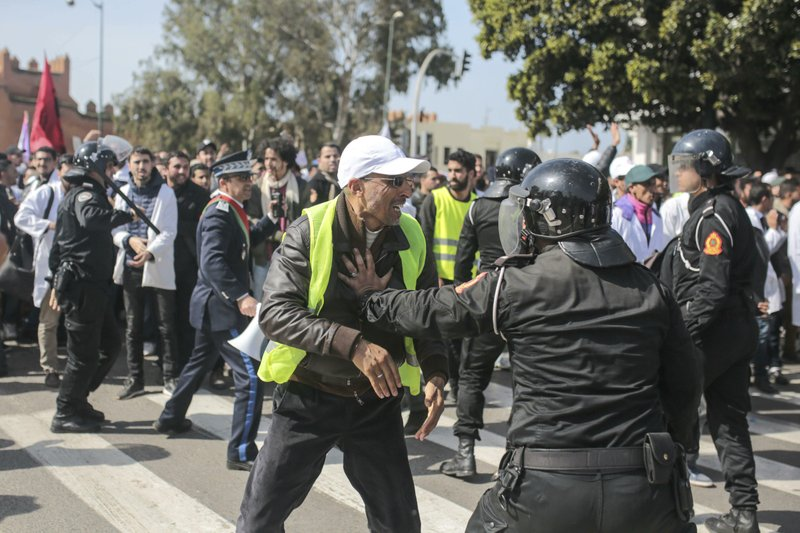 A teacher wearing a yellow vest is confronted by security forces during a demonstration in Rabat, Morocco, Wednesday, Feb. (AP Photo/Mosa'ab Elshamy)