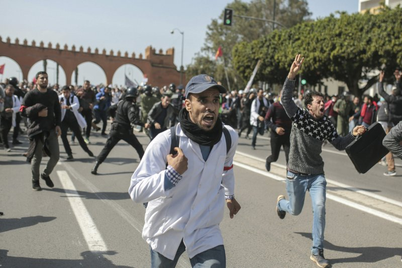 Protesting teachers run from security forces attempting to disperse a demonstration in Rabat, Morocco, Wednesday, Feb. (AP Photo/Mosa'ab Elshamy)