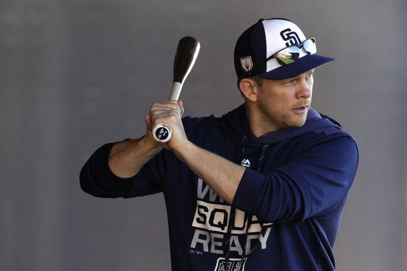 San Diego Padres manager Andy Green stands in as batter as a pitcher throws during spring training baseball practice Saturday, Feb. (AP Photo/Charlie Riedel)
