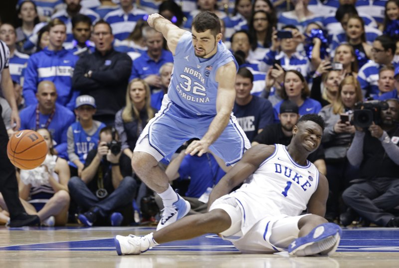 Duke's Zion Williamson (1) falls to the floor with an injury while chasing the ball with North Carolina's Luke Maye (32) during the first half of an NCAA college basketball game in Durham, N. (AP Photo/Gerry Broome)