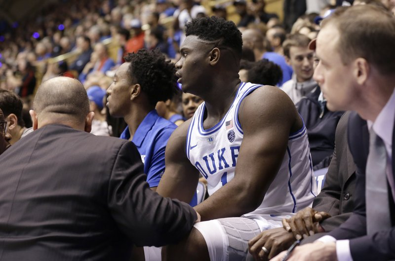 Duke's Zion Williamson (1) is attended to on the bench following an injury during the first half of an NCAA college basketball game against North Carolina in Durham, N. (AP Photo/Gerry Broome)