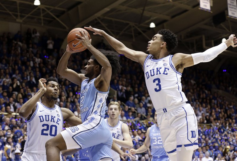 Duke's Marques Bolden (20) and Tre Jones (3) guard North Carolina's Coby White (2) during the first half of an NCAA college basketball game in Durham, N. (AP Photo/Gerry Broome)