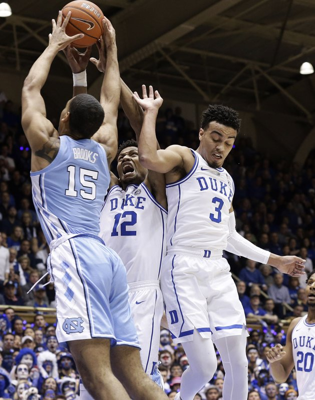 Duke's Javin DeLaurier (12) and Tre Jones (3) guard North Carolina's Garrison Brooks (15) during the first half of an NCAA college basketball game in Durham, N. (AP Photo/Gerry Broome)