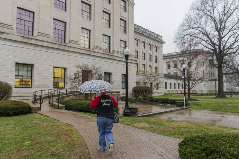 A supporter of the teachers strike walks toward the West Virginia State Capitol in Charleston, W.Va. on the second day of a statewide strike by teachers and school personnel on Tuesday, February 20, 2019. (Craig Hudson/Charleston Gazette-Mail via AP)