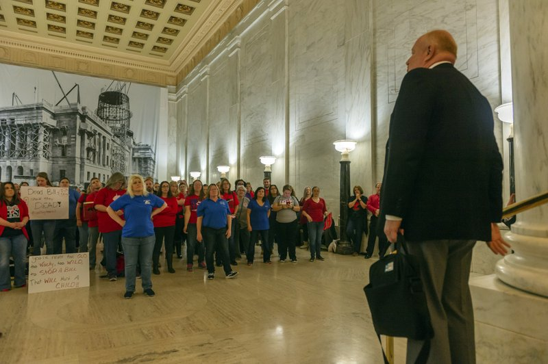 CORRECTS DAY OF WEEK TO WEDNESDAY - Teachers and school personnel, on the second day of a statewide strike, listen as West Virginia Education Association President Dale Lee speaks  outside the House of Delegates chamber, Wednesday, Feb. (Craig Hudson/Charleston Gazette-Mail via AP)