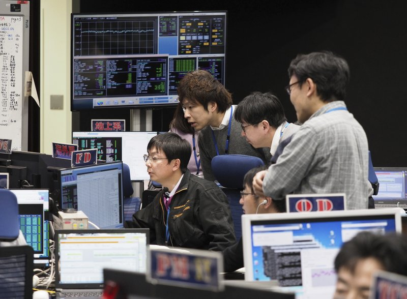 In this photo provided by the Japan Aerospace Exploration Agency (JAXA), staff of the Hayabusa2 Project watch monitors for a safety check at the control room of the JAXA Institute of Space and Astronautical Science in Sagamihara, near Tokyo, Thursday, Feb. (170 million miles) from Earth. JAXA said Thursday that Hayabusa2 began its approach at 1:15 p.m. (ISAS/JAXA via AP)