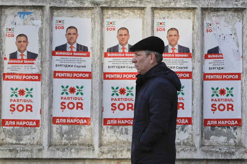 A man walks by electoral posters advertising the candidates of the the Show party, led by Israeli born Modovan businessman Ilan Shor, in Chisinau, Moldova, Thursday, Feb. (AP Photo/Vadim Ghirda)