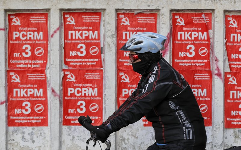 A man rides a bicycle by electoral posters advertising the Communist party in Chisinau, Moldova, Thursday, Feb. (AP Photo/Vadim Ghirda)